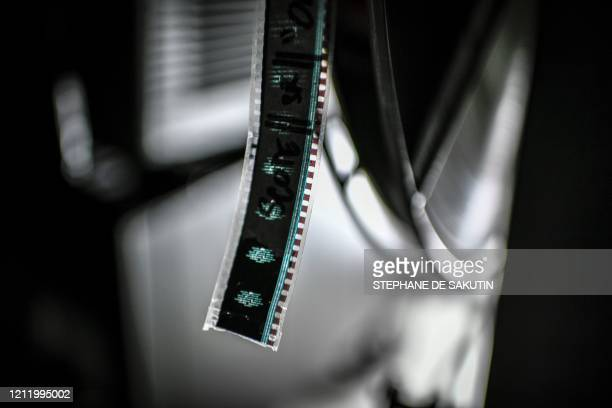 This picture taken on May 6 2020 shows a 35 mm film in the projection room of the Cinema Grand Action movie theatre in Paris as the country is under...