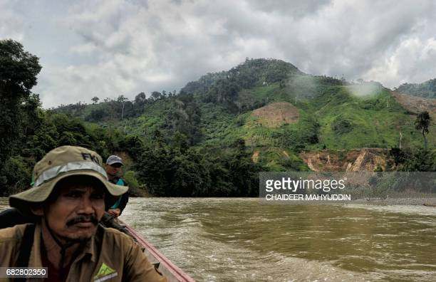 This picture taken on May 7 2017 shows a team of Indonesian forest rangers making their way along the Alas river as signs of deforestation from...