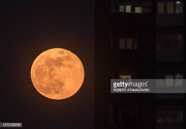 This picture taken on May 7 2020 shows the May's full Moon known as the Full Flower Moon rises over Skopje on May 7 2020 The May full moon is...
