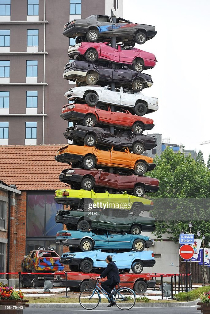 This picture taken on May 8, 2013 shows a sculpture made of 13 retired cars in 'Jiangcheng No.1' Creative Culture Park in Wuhan, central China's Hubei province. The sculpture, 'Rebirth 2013', is placed inside the park that used to be a factory back in last century. The first walking tractor of China was produced here in the factory in 1957. CHINA