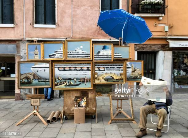 TOPSHOT This picture taken on May 9 2019 in Venice shows an unnamed man supposed to be British street artist Banksy siting next to a montage of oil...