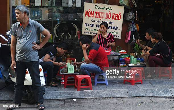 This picture taken on November 1 2013 shows people eating 'nom' or papaya salad with beef a very popular street food on a street in the old quarter...