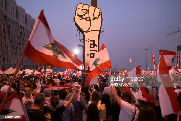 """This picture taken on November 10, 2019 shows protesters waving Lebanese national flags by a giant sign of a fist with the slogan """"revolution""""..."""