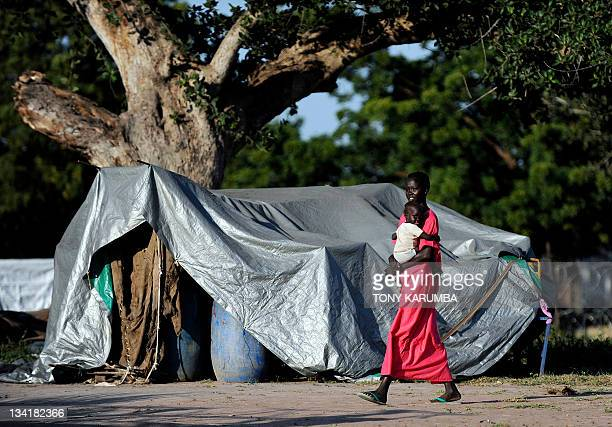 This picture taken on November 12 2011 shows a south Sudanese woman with her child who are transiting from north Sudan walk past a shelter at a...