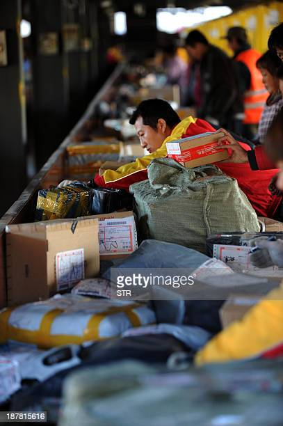 This picture taken on November 12 2013 shows workers sorting out packages at an express delivery company in Beijing Chinese shoppers spent a record...