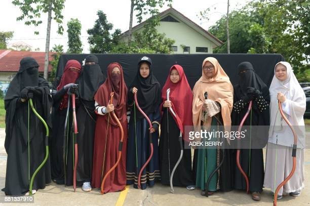 This picture taken on November 12, 2017 shows Indonesian Muslim women posing for a photograph after participating in archery and horse riding lessons...