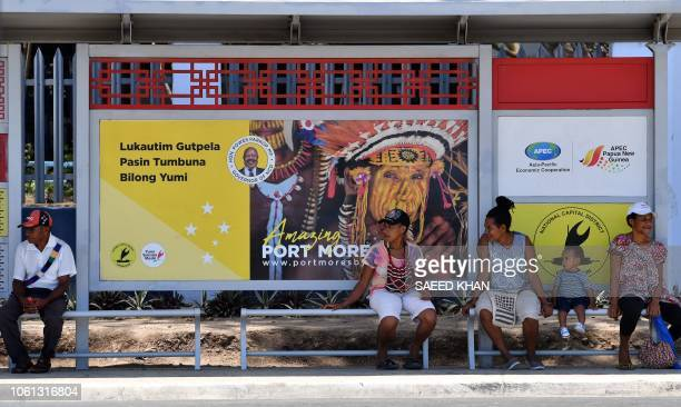 This picture taken on November 13 2018 shows residents waiting at a bus stop donated by China in downtown Port Moresby ahead of the AsiaPacific...