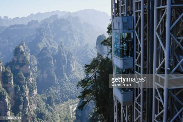 This picture taken on November 13, 2020 shows tourist taking the Bailong elevators in Zhangjiajie, China's Hunan province. - Towering more than 300...