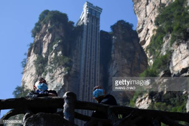 This picture taken on November 13, 2020 shows two tourists wearing face masks looking out in front of the Bailong elevators in Zhangjiajie, China's...