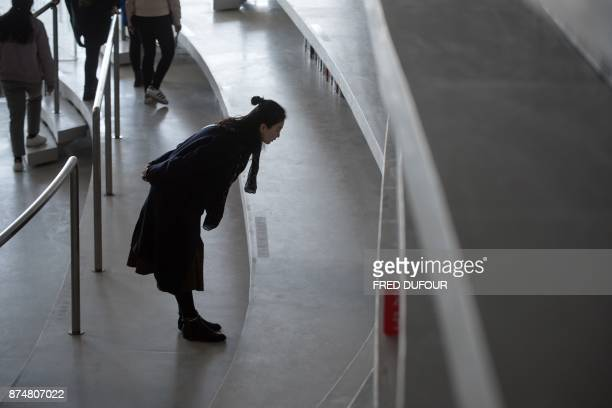This picture taken on November 14 2017 shows a woman looking at books at the Tianjin Binhai Library A futuristic Chinese library has wowed book...
