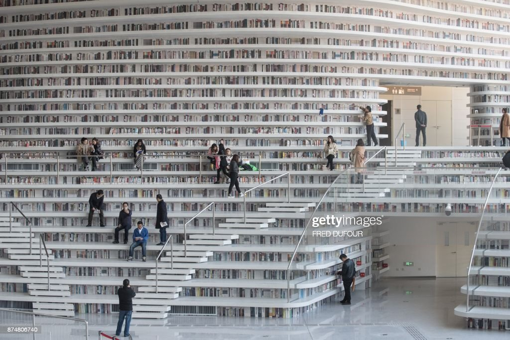 TOPSHOT - This picture taken on November 14, 2017 shows people visiting the Tianjin Binhai Library. A futuristic Chinese library has wowed book lovers around the world with its white, undulating shelves rising from floor to ceiling, but if you read between the lines you'll spot one problem. Those rows upon rows of book spines are mostly images printed on the aluminium plates that make up the backs of shelves. / AFP PHOTO / FRED DUFOUR / To go with AFP story China-library-architecture, FOCUS by Becky Davis