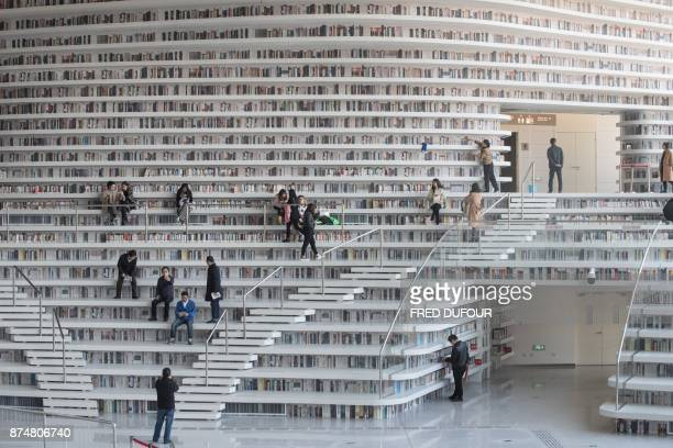 TOPSHOT This picture taken on November 14 2017 shows people visiting the Tianjin Binhai Library A futuristic Chinese library has wowed book lovers...