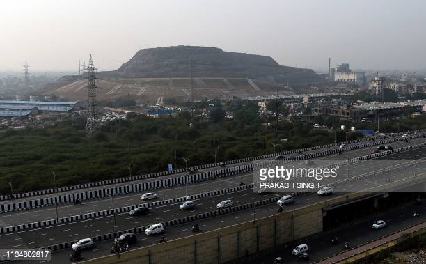 This picture taken on November 15 shows a highway in front of the Ghazipur landfill site in New Delhi The Indian capital generates around 9000 metric...