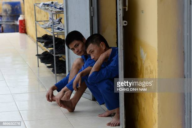 This picture taken on November 16 2017 shows two inmates sitting the door of their dormitory before lunchtime inside a drug rehabilitation centre in...