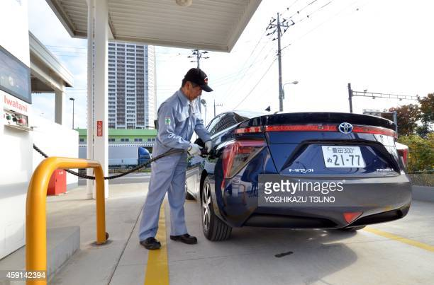 This picture taken on November 17 2014 shows a man refueling Japanese auto giant Toyota Motor's fuel cell vehicle 'Mirai' meaning future at a...