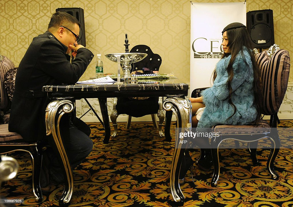 This picture taken on November 18, 2012 shows a woman accepting an interview during a matchmaking event for China's multi-millionaires in Wuhan, central China's Hubei province. This matchmaking event arranged by the China Entrepreneur Club for Singles received the participation of 169 women in Wuhan, while only 5 of them pass all the tests for the first round selection. CHINA
