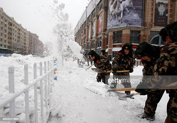 This picture taken on November 18 2013 shows soldiers clearing snow from a street in Harbin northeast China's Heilongjiang province Northeastern...