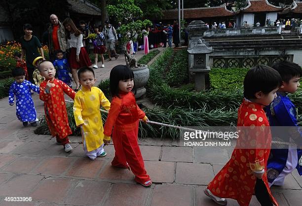 This picture taken on November 18 2014 shows children from a local kindergarten wearing Vietnamese 'ao dai' traditional festive dresses walking in...