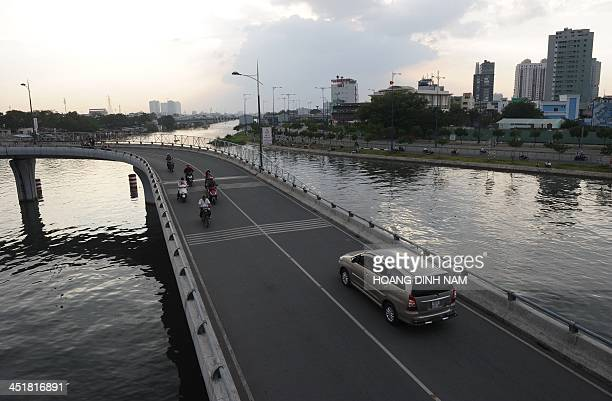 This picture taken on November 19 2013 shows a car and motorcyclists riding on a newly built bridge over Saigon river in Ho Chi Minh city With funds...