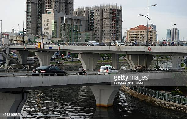 This picture taken on November 19 2013 shows cars and motorcyclists riding on a newly built bridge over Saigon river in Ho Chi Minh city With funds...