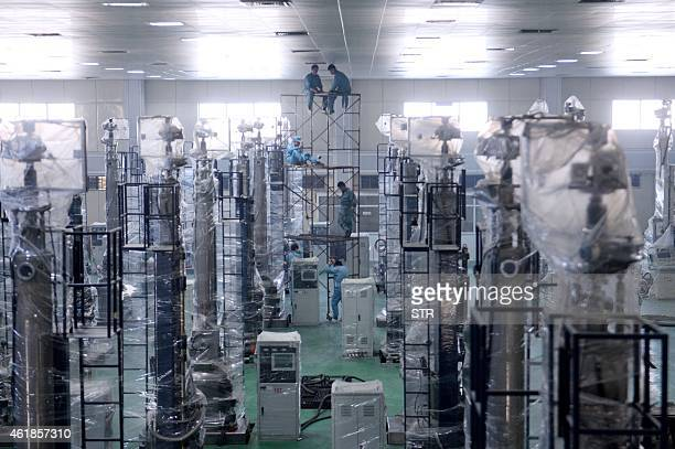 This picture taken on November 19 2015 shows laborers working in a workshop at Jinglong group in Ningjin central China's Hebei province China's...