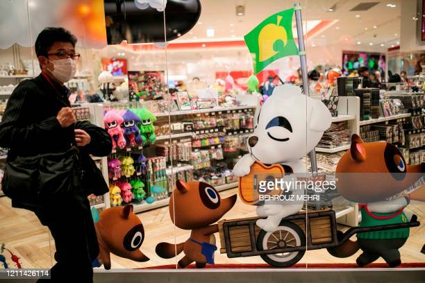 This picture taken on November 19, 2019 shows a man wearing a face mask as he walks past Nintendo game characters from the Animal Crossing series of...