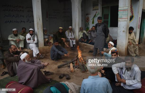 This picture taken on November 2 2017 shows Pakistani hashish smokers sitting around a fire at a shrine for Sufi poet Rahman Baba in Peshawar In...