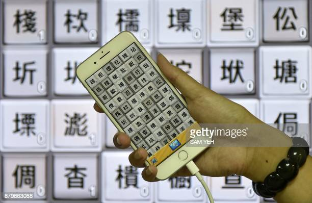 This picture taken on November 2 2017 shows Steve Tsai an APP designer of Zihun displaying his smart phone showing traditional Chinese characters...