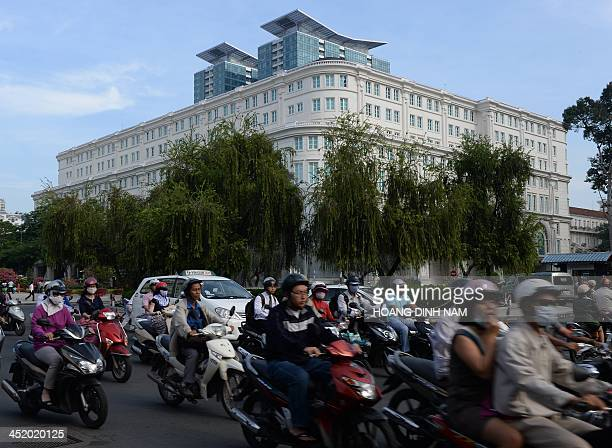 This picture taken on November 20 2013 shows motorcyclists riding past the newly built luxury shopping center Union Square in Ho Chi Minh City The...