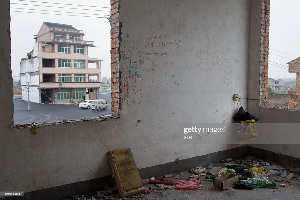 This picture taken on November 22, 2012 shows a half-demolished apartment building (L) standing in the middle of a newly-built road thanks to a Chinese couple that refused to move in Wenling, in eastern China's Zhejiang province. Luo Baogen, 67, and his 65-year-old wife have waged a four-year battle to receive more than the 41,300 USD compensation offered by the local government of Daxi, a Chinese newspaper said. The phenomenon is called a 'nail house' in China, as such buildings stick out and are difficult to remove, like a stubborn nail. CHINA