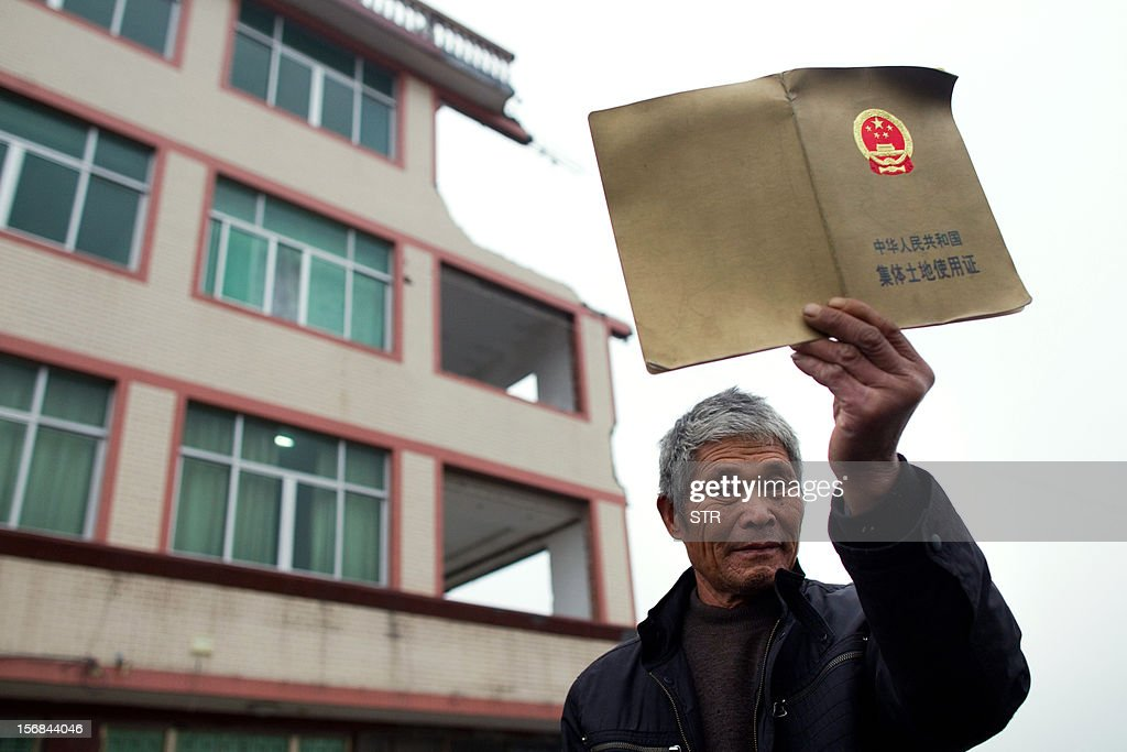 This picture taken on November 22, 2012 shows Luo Baogen showing a permit to the collectively-owned land as he stands before his half-demolished apartment building that stands in the middle of a newly-built highway in Wenling, in eastern China's Zhejiang province. Luo Baogen, 67, and his 65-year-old wife have waged a four-year battle to receive more than the 41,300 USD compensation offered by the local government of Daxi, a Chinese newspaper said. The phenomenon is called a 'nail house' in China, as such buildings stick out and are difficult to remove, like a stubborn nail. CHINA