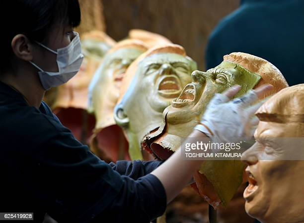 This picture taken on November 22, 2016 shows an employee putting a rubber mask of US President-elect Donald Trump onto the painting line at the...