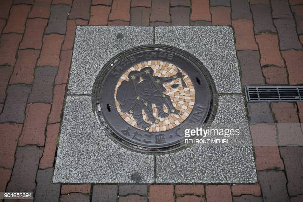 This picture taken on November 22 2017 shows a manhole cover designed as Gemini third astrological sign in the Zodiac in Kawaguchi Saitama prefecture...
