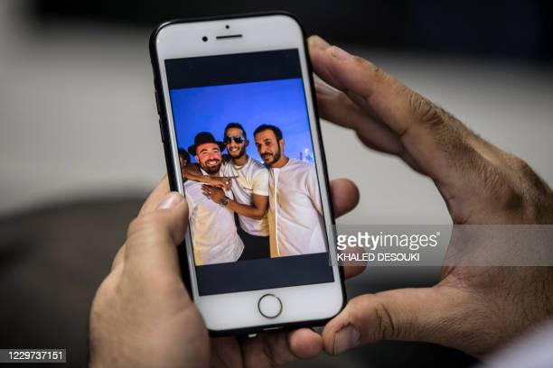 """This picture taken on November 22, 2020 in Cairo shows a man holding a phone showing a picture of Egypt's self-proclaimed """"superstar"""" Mohamed Ramadan..."""