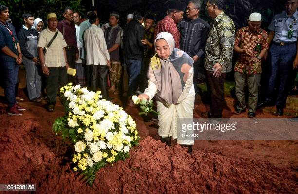 This picture taken on November 23 2018 shows a woman placing flowers on her husband's grave who died in the illfated Lion Air flight JT 610 during...