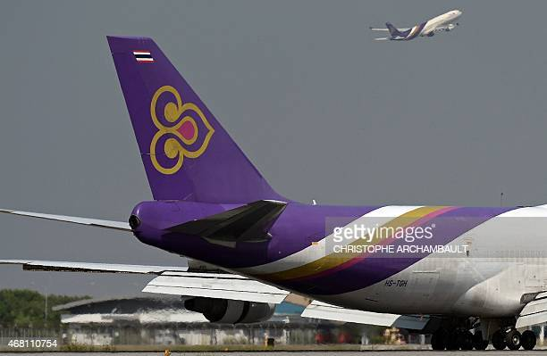 This picture taken on November 24 2014 shows a Thai Airways aircraft taking off past the tail of a cargo Thai Airways plane at Bangkok's Suvarnabhumi...