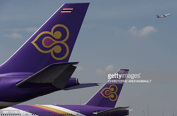 This picture taken on November 24 2014 shows a Thai Airways aircraft taking off past the tails of two other Thai Airways planes at Bangkok's...