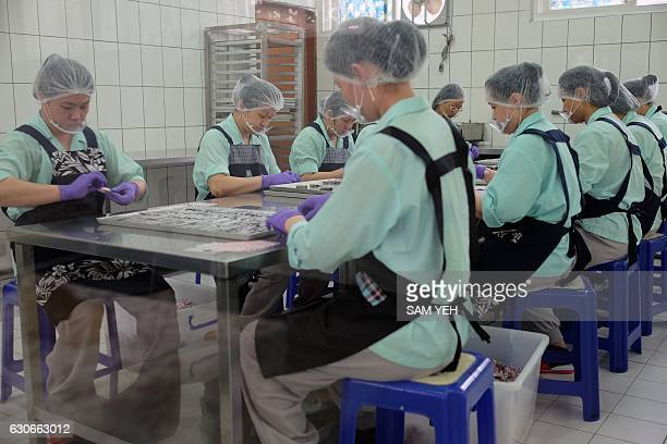 This picture taken on November 24 2016 shows prisoners packing candy at a correctional facility in Taoyuan northern Taiwan If it were not for the...