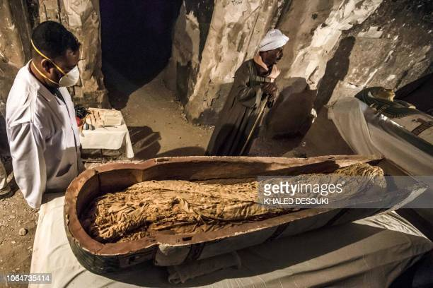This picture taken on November 24 2018 shows Egyptian workers and archaeologists standing next to an opened intact sarcophagus containing a...