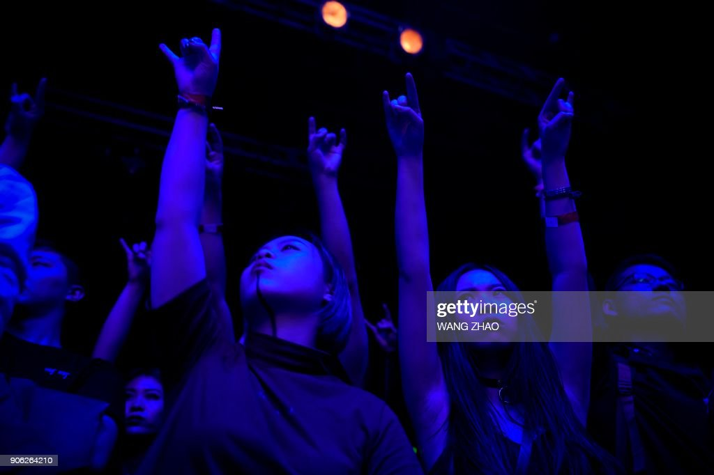 This picture taken on November 25, 2017 shows fans gesturing during a performance by metal band Zuriaake at a club in Beijing. Powered by cacophonous guitars and drums, the black metal band Zuriaake dips into the tenebrous depths of ancient Chinese culture to produce a unique blend of east and west. DAVIS
