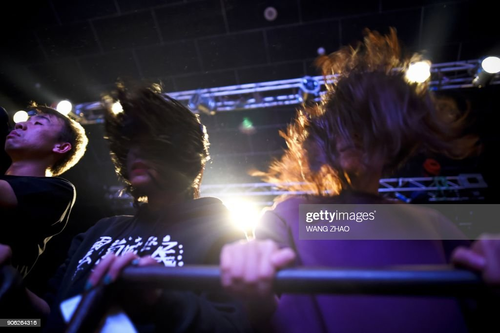 This picture taken on November 25, 2017 shows fans headbanging during a metal rock band performance at a club in Beijing. Powered by cacophonous guitars and drums, the black metal band Zuriaake dip...