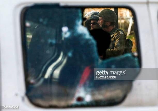 TOPSHOT This picture taken on November 26 2018 shows Israeli soldiers standing by a damaged car at the scene of an attack where a Palestinian man...