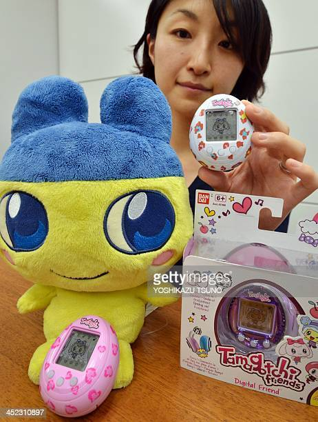 This picture taken on November 27 2013 shows Japanese toy giant Bandai employee Tomomi Washizu displaying the new Tamagotchi virtual pet toy release...