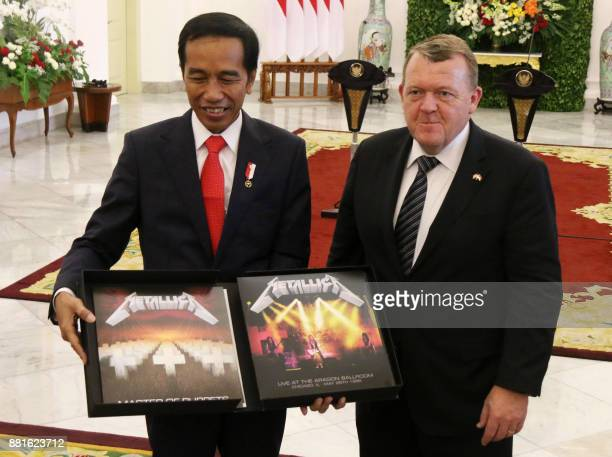 This picture taken on November 28 2017 shows Indonesian President Joko Widodo displaying a box set of Metallica's Master of Puppets a gift from...