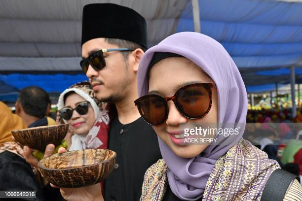 This picture taken on November 28 2018 shows Indonesians holding cups of Kawa Daun coffee served in coconut shells during the Minangkabau arts and...