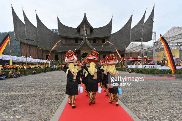 This picture taken on November 28 shows Indonesian women carrying trays contained foods on their head for eating tradition namely Bajamba during an...