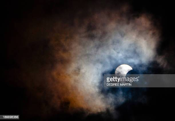 This picture taken on November 3 2013 shows a rare hybrid solar eclipse through clouds from the Canary Island of Tenerife A rare solar eclipse swept...