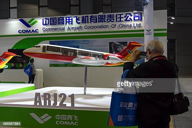This picture taken on November 3 2015 shows a visitor taking photos of a model of an Chinesemade Comac ARJ21 passenger aircraft at the 17th China...