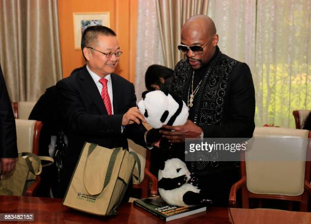 This picture taken on November 30 2017 shows US boxer Floyd Mayweather receiving a stuffed panda toy during an adoption ceremony after he adopted a...