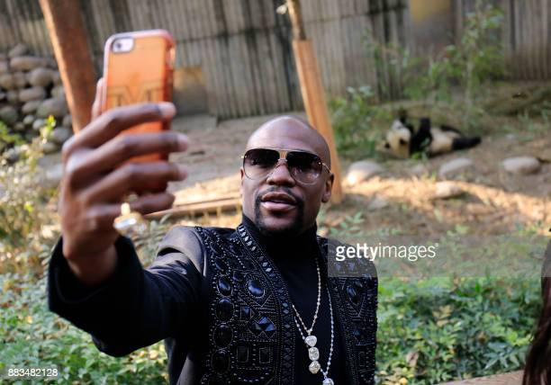 This picture taken on November 30 2017 shows US boxer Floyd Mayweather posing for a selfie by a panda enclosure as he visits the Chengdu Research...